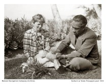 Duke shows Amelia Earhart how to peel a pineapple